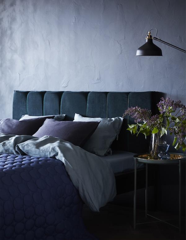 Ein MALM Bettgestellt von IKEA kannst du wunderbar in ein Bett mit selbst gepolstertem Kopfteil verwandeln. Wir haben das mit etwas Schaumschoff und einer dunkelblauen Samtgardine getan.