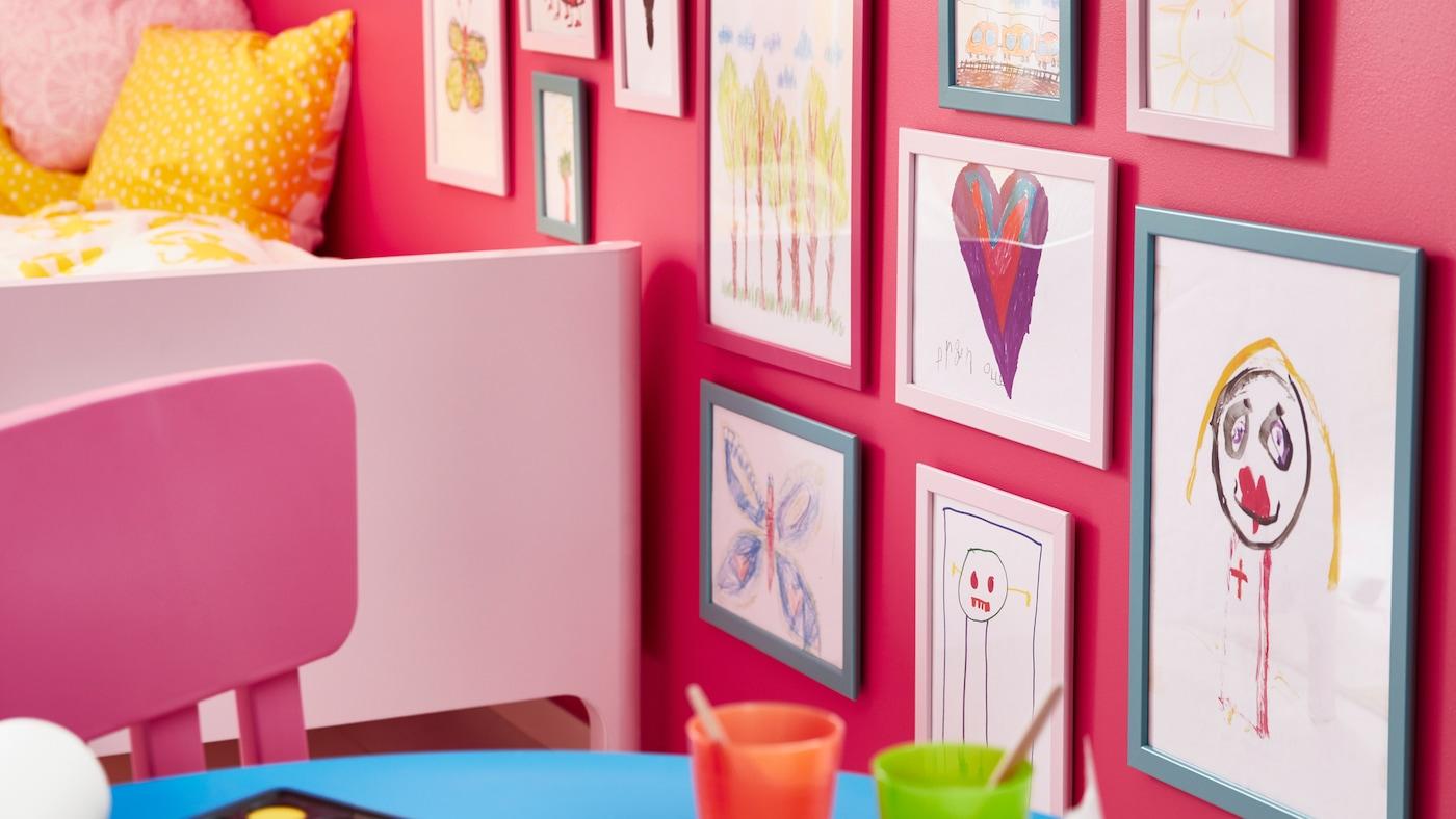 Ein MAMMUT Kinderstuhl in Rosa steht neben einem BUSUNGE Bettgestell und einer Wand mit verschiedenen FISKBO Rahmen, in denen Kinderzeichnungen zu sehen sind.