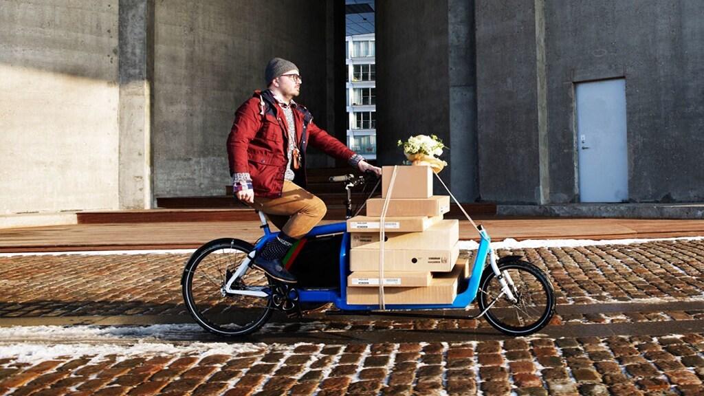Ein Mann auf einem Fahrrad, das vorne Platz für mehrere Pakete zum Ausliefern hat