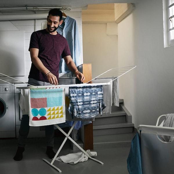 Ein Mann hängt im Keller Wäsche an MULIG Wäschetrockner auf.
