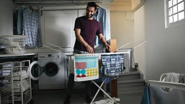 Ein Mann hängt Wäsche auf einen Wäscheständer auf