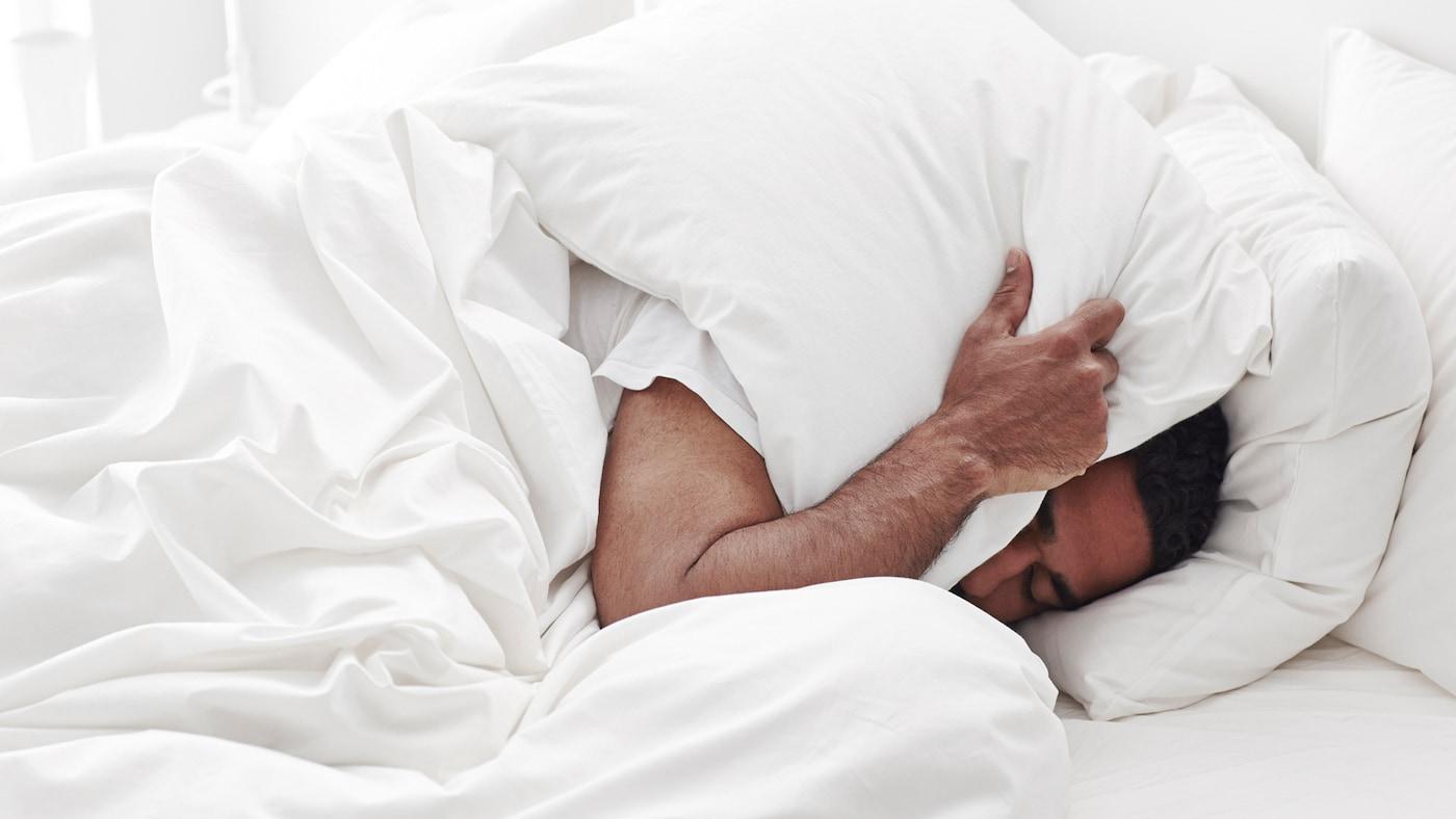 Ein Mann liegt im Bett und drückt einen weißen Polster auf sein Gesicht