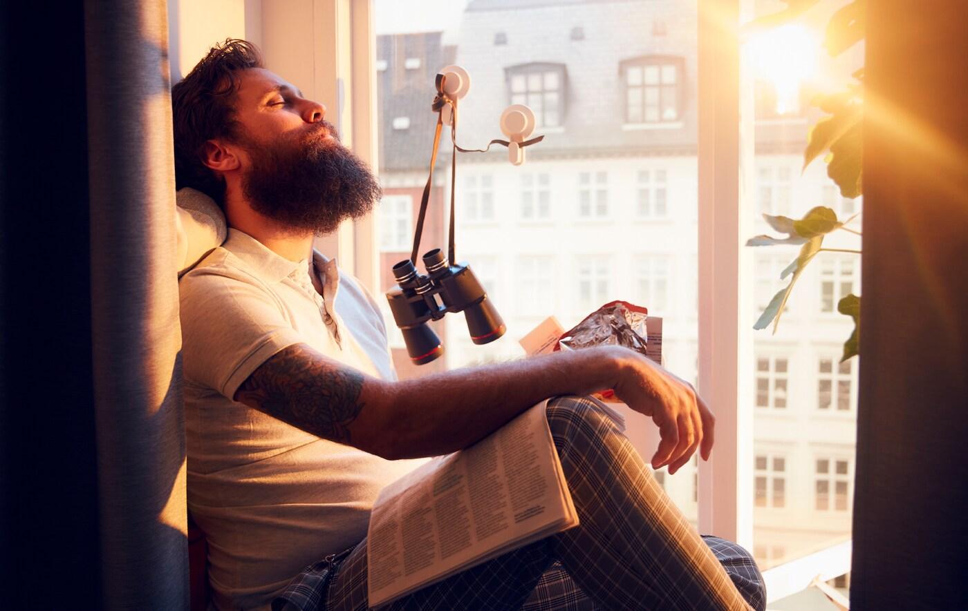 Ein Mann mit Bart sitzt auf einer breiten Fensterbank in der Sonne und lehnt den Kopf an die Wand. Im Hintergrund ist ein Mehretagenhaus zu sehen.