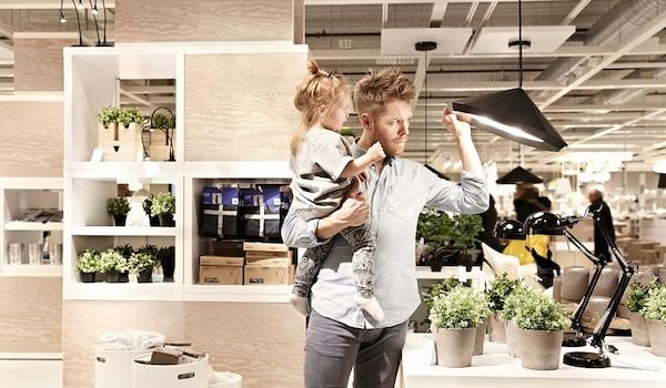Ein Mann mit einem kleinen Mädchen auf dem Arm hebt in der Möbelaustellung eine schwarze Hängelampe an, um darunter zu schauen