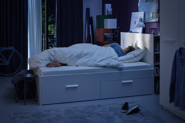 Ein Mann schläft gemütlich im Bett.