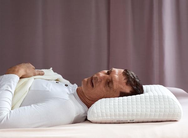 Ein Mann schläft tief und fest auf dem Rücken auf einem ergonomischen IKEA RUMSMALVA Kissen für Seiten-/Rückenschläfer.