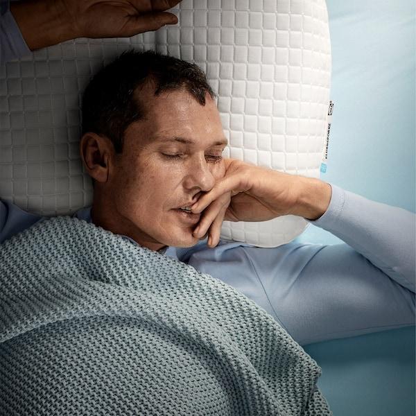 Ein Mann schläft tief und fest auf dem Rücken liegend auf einem ergonomischen IKEA KLUBBSPORRE Kissen für alle Schlafpositionen.