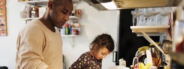 Ein Mann steht in einer Küche am Herd und brät Gemüse. Ein Kind steht neben ihm und hilft ihm mit den Vorbereitungen. Auf der Arbeitsfläche befinden sich eine Flasche Öl, Eier und Schüsseln.
