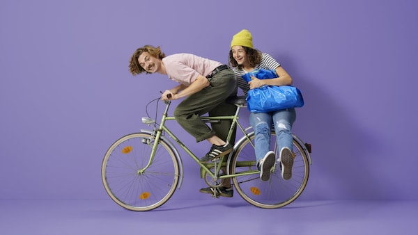 Ein Mann und eine Frau sitzen auf einem Fahrrad um Ihre IKEA Einkäufe zu transportieren.