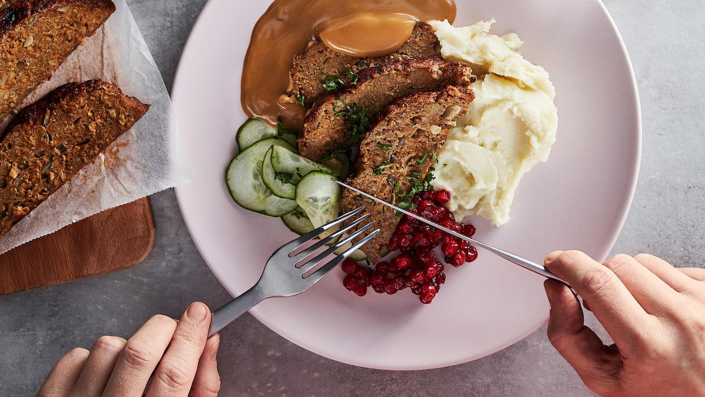 Ein Messer und eine Gabel werden an einen Teller mit Hackbraten, Gurkenscheiben, Preiselbeeren, Rahmsosse und Kartoffelpüree herangeführt.