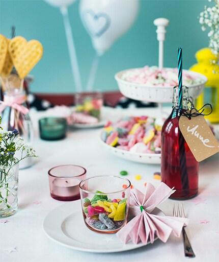 Ein mit Bonbonfarbenen Accessoires, Schleifen & Luftballons gedeckter Tisch