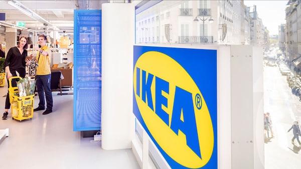 Ein Mitarbeiter im IKEA Einrichtungshaus zeigt einer Kundin den Weg im Einrichtunshaus