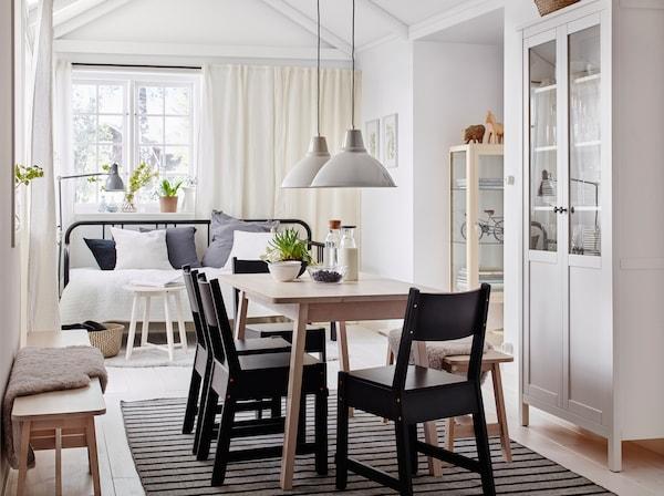 Ein mittelgroßes Esszimmer eingerichtet mit einem Esstisch in weiß lasierter Birke und NORRÅKER Stühlen in Schwarz