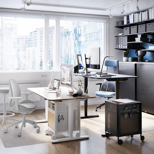 Ein moderner Büroraum mit zwei Stehpulten, der helle und dunklere Büromöbel zeigt.