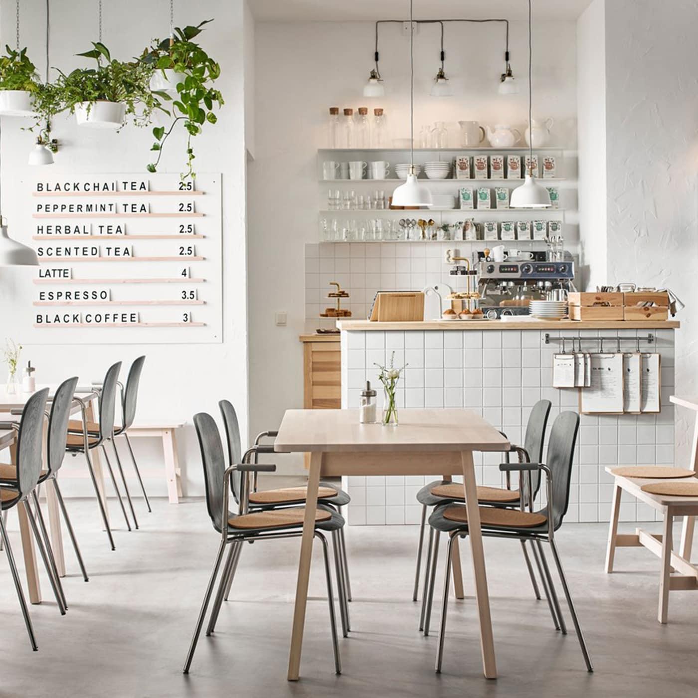 Ein modernes Café in beige, schwarz und weiß mit NORRÅKER Tischen in weißer Birke und SVENBERTIL Armlehnstühlen in schwarz mit verchromtem DIETMAR Untergestellen für Armlehnstuhl.