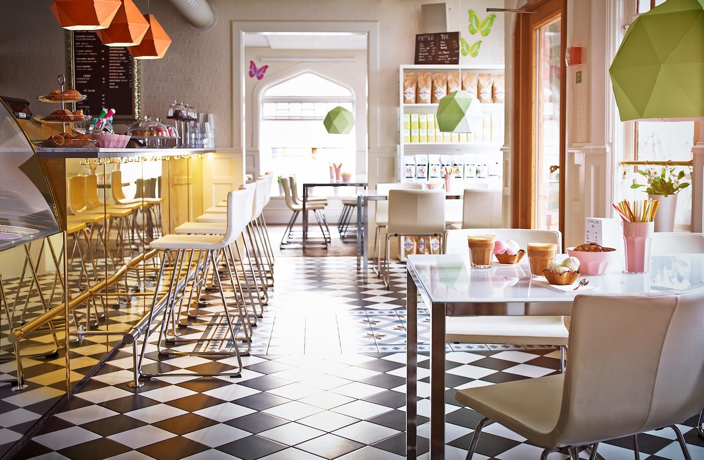 Ein modernes Café mit Eisdiele mit weißen BERNHARD Stühlen & Tischen mit weißen Platten aus Glas
