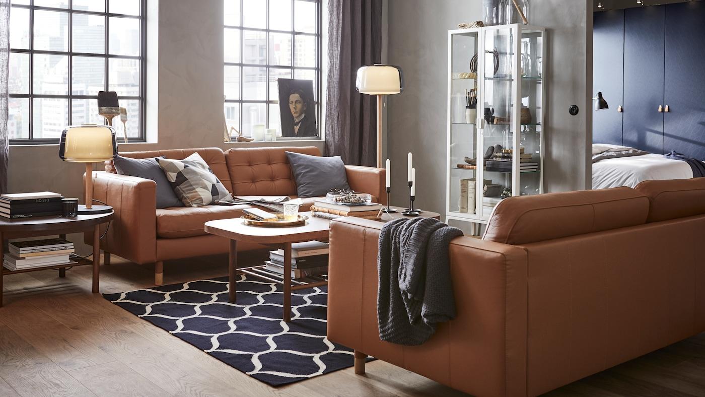 Ein modernes Wohnzimmer mit Vitrine, braunen Ledersofas und runden Couchtischen.