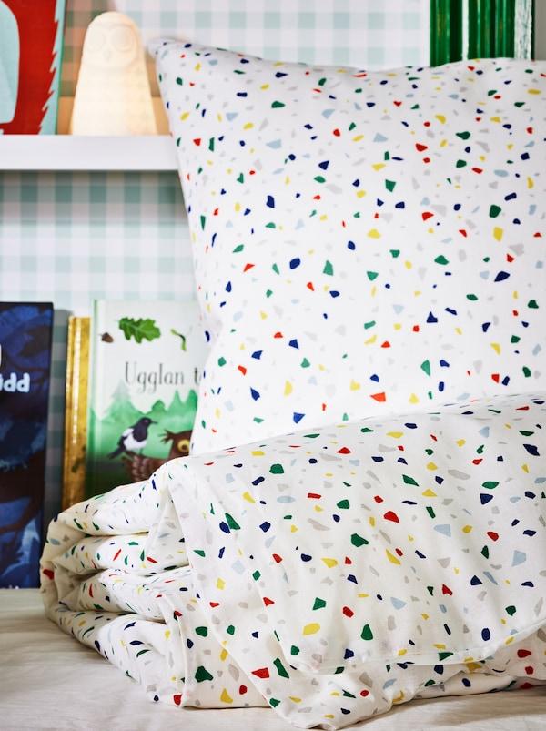 Ein MÖJLIGHET Bettwäscheset auf einem ungemachten Bett mit einer SOLBO LED-Leuchte und Büchern an der Wand dahinter.