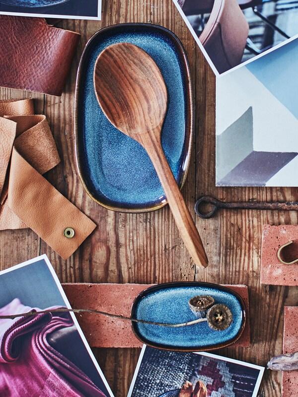 Ein Moodboard mit einem Holzlöffel, einer dunkelblauen, ovalen Schale, ein paar Fotos, Stoff- und Lederstücken, Haken und einer Küchenfliese.