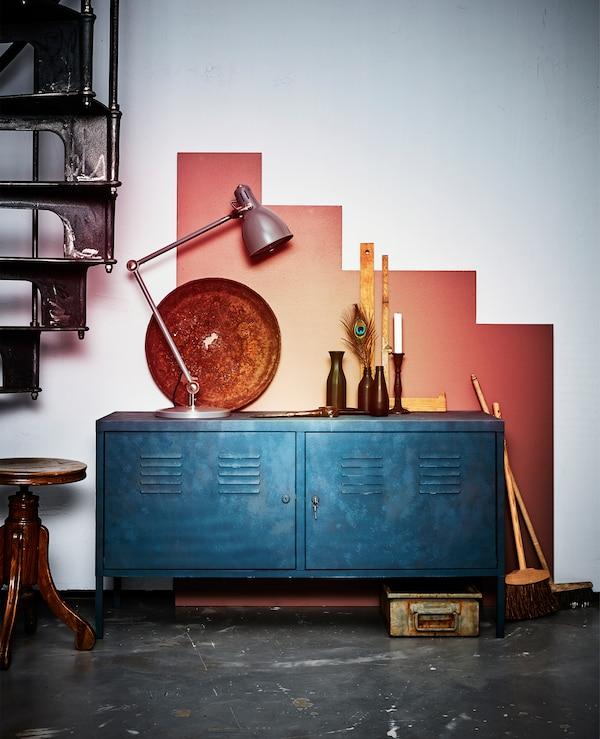 Ein neu gestrichener PS Schrank in Blau steht an einer grafisch gestalteten Wand