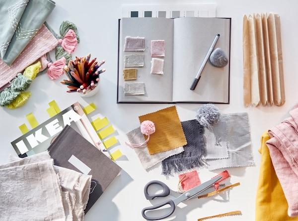 Ein Notizbuch, ein Stift, eine Schere, Stoffstücke in Rosa, Grau, Gelb, Senfgelb und Grün liegen neben einem teilweise verdeckten IKEA Katalog 2021.