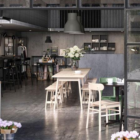 Ein offen gestaltetes Café inklusive Laden und Gemeinschaftsbereich, das von offen stehenden Glastüren eingerahmt wird. Auf dem Tisch und an den Türen stehen Blumen.