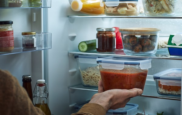 Ein offener Kühlschrank, u. a. mit IKEA 365+ Vorratsbehältern mt Deckel, quadratisch Glas, in denen verschiedene Lebensmittel zu sehen sind.