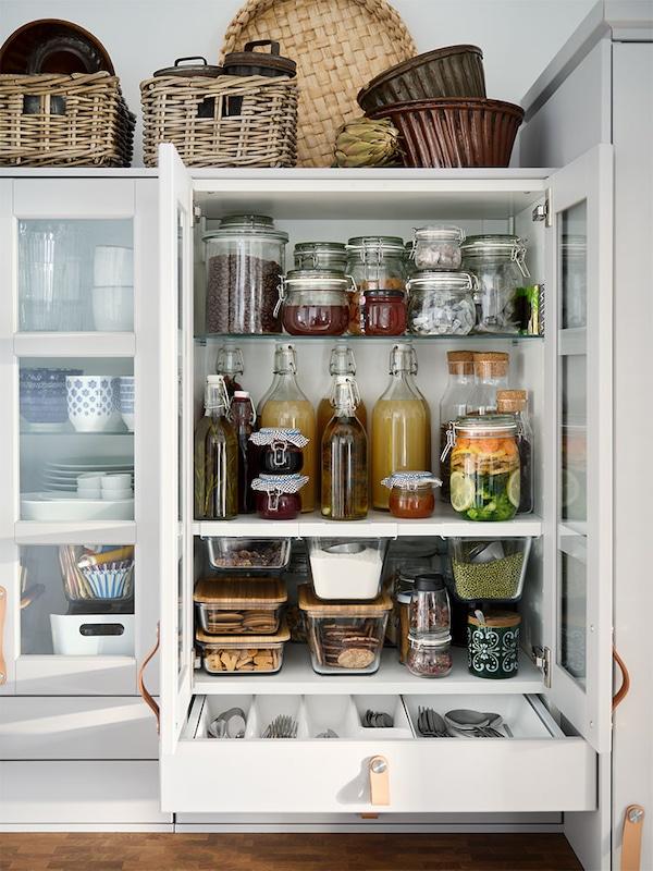 Ein offener Schrank mit Regalen und einer Schublade, in denen Vorräte ordentlich und nachhaltig in Vorratsbehältern sortiert sind.