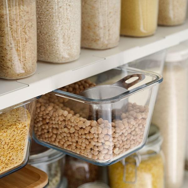 Ein offener Schrank mit Regalen und Einschubfächern, in denen Vorräte ordentlich und nachhaltig in Glasbehältern sortiert sind.