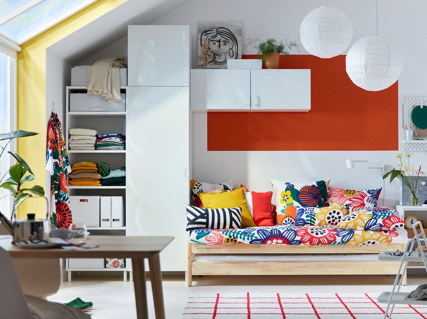 Ein offener Wohnbereich mit einem Bett mit vielen bunten Kissen, weißen Schränken & einem Tisch.