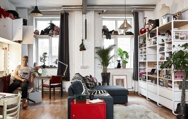Ein offener Wohnbereich mit hoher Zimmerdecke, einem L-förmigen Sofa und Wandaufbewahrung. Donald sitzt auf einem Stuhl vor einem Spiegel.