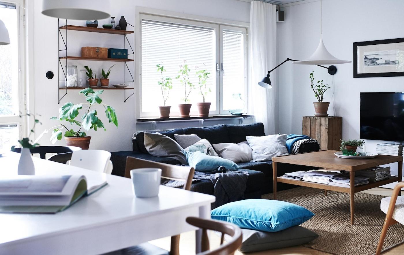 Ein offenes Wohnzimmer mit moderner Einrichtung, wie einem grauen Sofa, einem Tisch, Stühlen und Kissen.