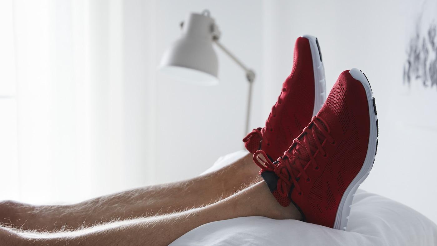 Ein paar Füße liegen mit roten Turnschuhen bekleidet auf einem Stapel weißer Kissen. Im Hintergrund ist eine weiße Leuchte zu erkennen.