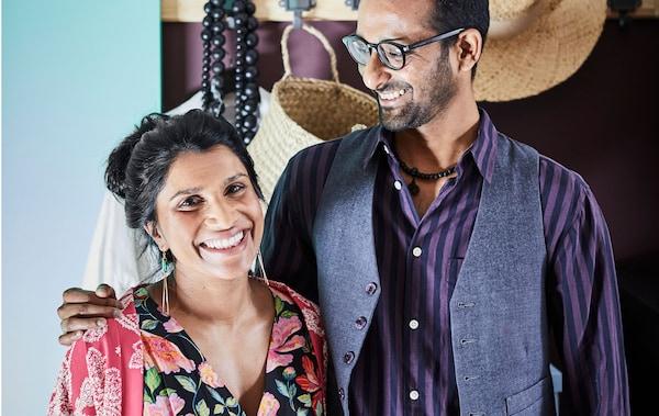 Ein Paar lächelt glücklich in die Kamera. Hinter ihnen ist Deko ihrer ersten gemeinsamen Wohnung zu sehen