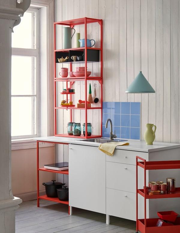 Ein paar rote und weiße ENHET Küchenschränke in einer Küche mit buntem Geschirr