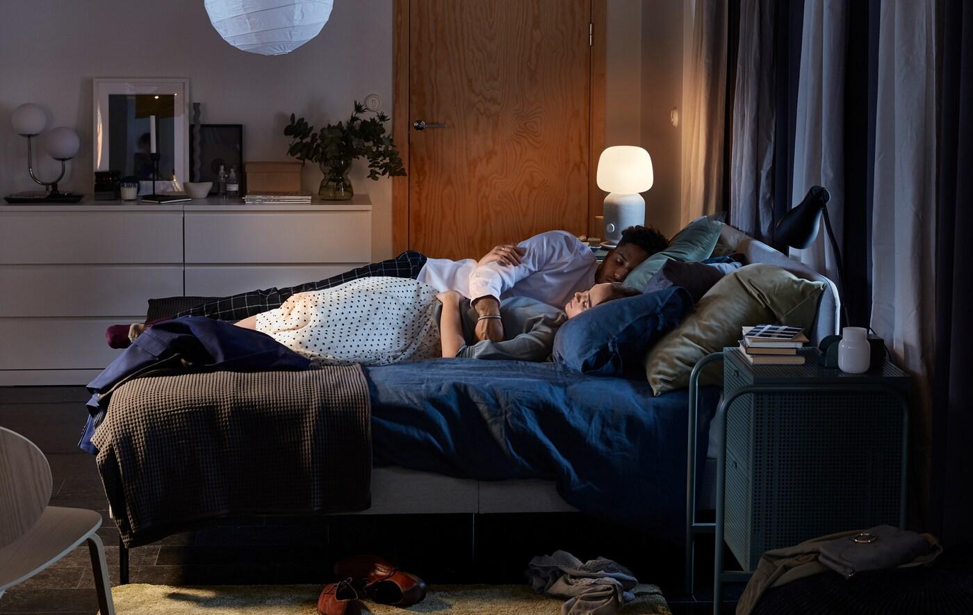 Ein Paar schläft in einem SLATTUM Bett mit blauer Bettwäsche, im Hintergrund ist eine SYMFONISK Leuchte und WiFi-Speaker zu sehen.