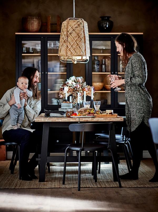 Ein Paar sitzt mit einem Baby am Esstisch. An der Wand sind dunkle Vitrinen mit Geschirr zu sehen.