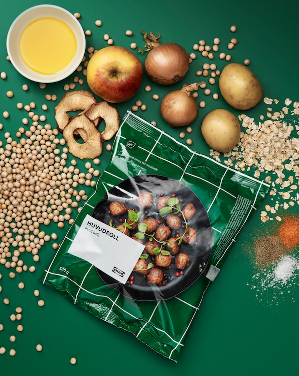 Ein Packung HUVUDROLL Proteinbällchen umgeben von den unverarbeiteten Zutaten: Erbsen, Haferflocken, Kartoffeln, Zwiebeln, Äpfel und Gewürze.
