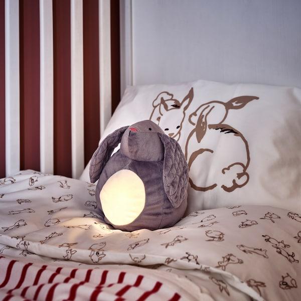Ein PEKHULT Stofftier mit LED-Nachtlicht ist beleuchtet und liegt in einem Babybett mit Bettwäsche mit Kaninchenmuster in Weiß/Beige.