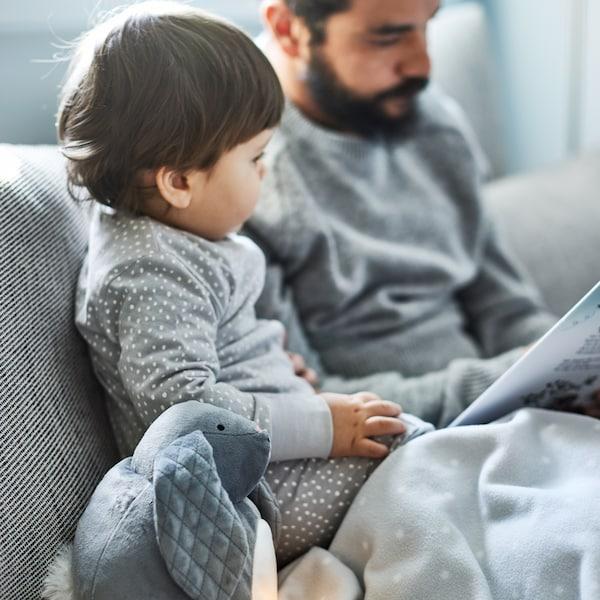 Ein PEKHULT Stofftier mit LED-Nachtlicht und eine LEN Babydecke liegen neben einem kleinen Kind, das seinem Vater zuhört, der ihm etwas vorliest. Beide sitzen auf einem Sofa in Beige/Braun.