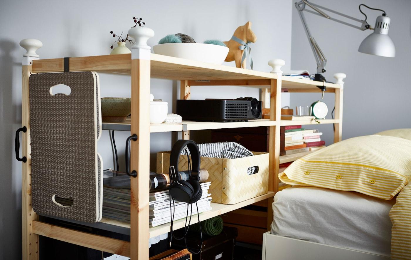 Ein personalisiertes IVAR Regal mit vielen Büchern & Accessoires hinter einem Bett