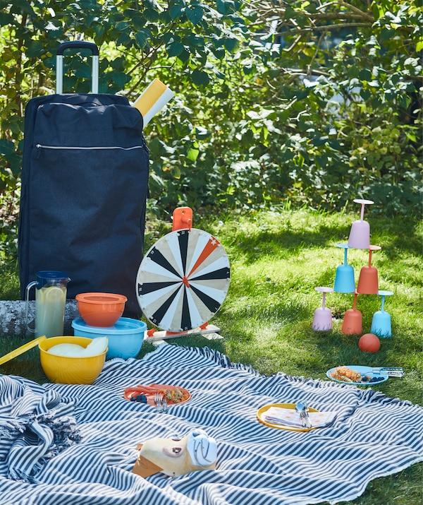 Ein Picknick im Gras mit Geschirr, Spielen und einer großen Decke. All das lässt sich leicht in der blauen FÖRENKLA Tasche auf Rollen transportieren.