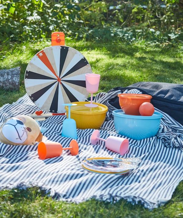 Ein Picknick im Gras mit robustem Geschirr aus Kunststoff und Weingläsern in verschiedenen Farben