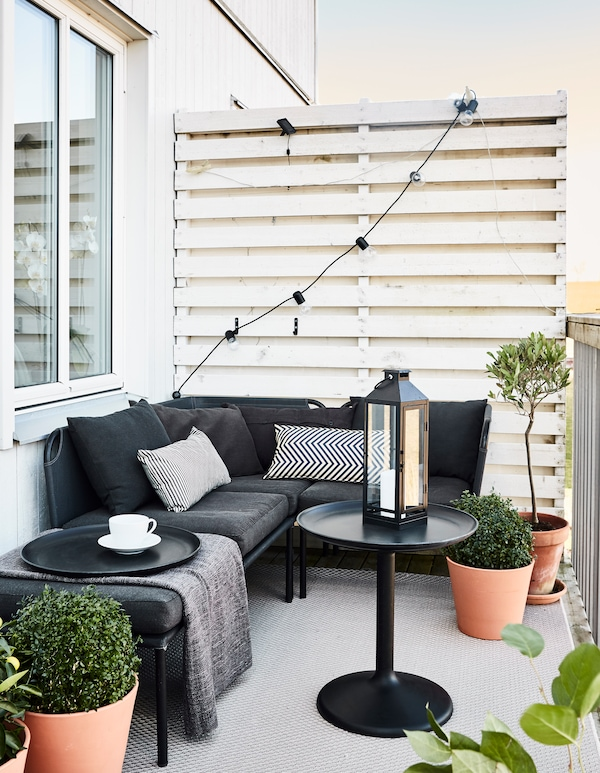 Ein Platz im Freien mit neutralfarbenen Möbeln, u. a. mit GRENÖ Kissen für draußen in Dunkelblau/Beige.