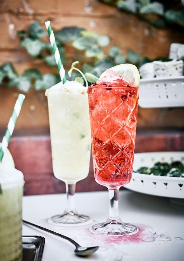 Ein Preiselbeer-Granatapfel-Cocktail steht zusammen mit einem anderen Cocktail auf einem Gartentisch.
