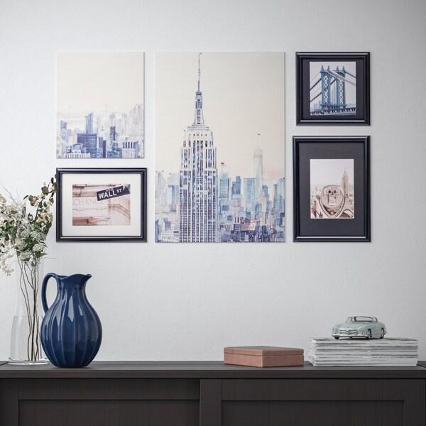 Ein RAMHÄLL Bild mit Rahmen 5er Set mit New York Motiven über einem Regal aus Holz.
