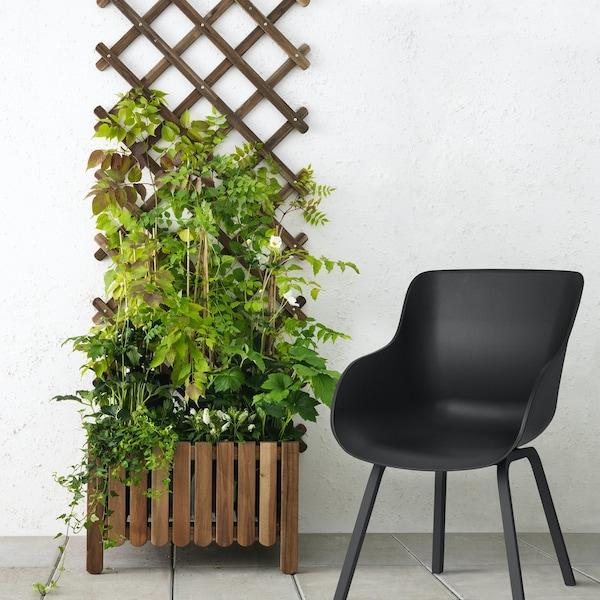 Ein Rankgitter vor einer weißen Wand, davor steht ein schwarzer, moderner Stuhl, der für den Einsatz innen und außen geeignet ist.