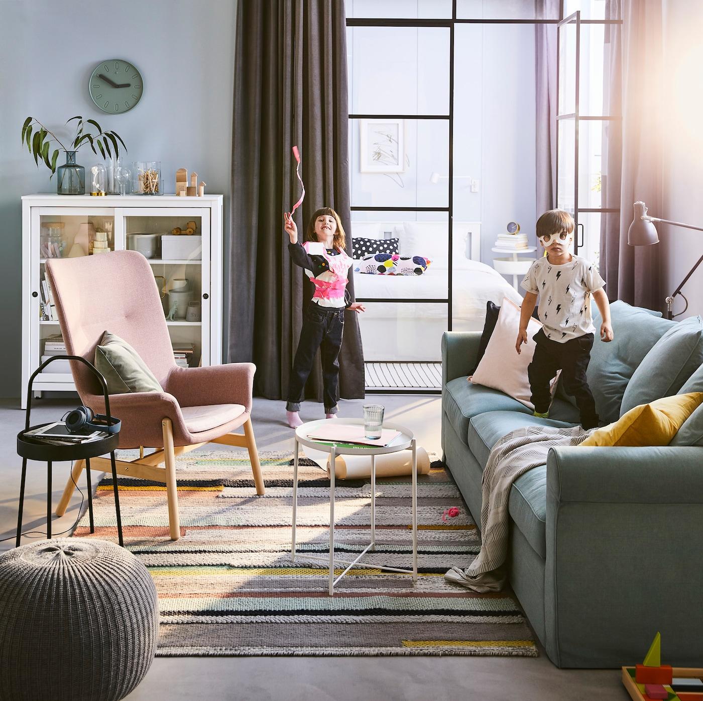Ein Raum Mit Einem Sofa, Einem Sessel Und Einer Vitrine, In Dem Zwei Kinder