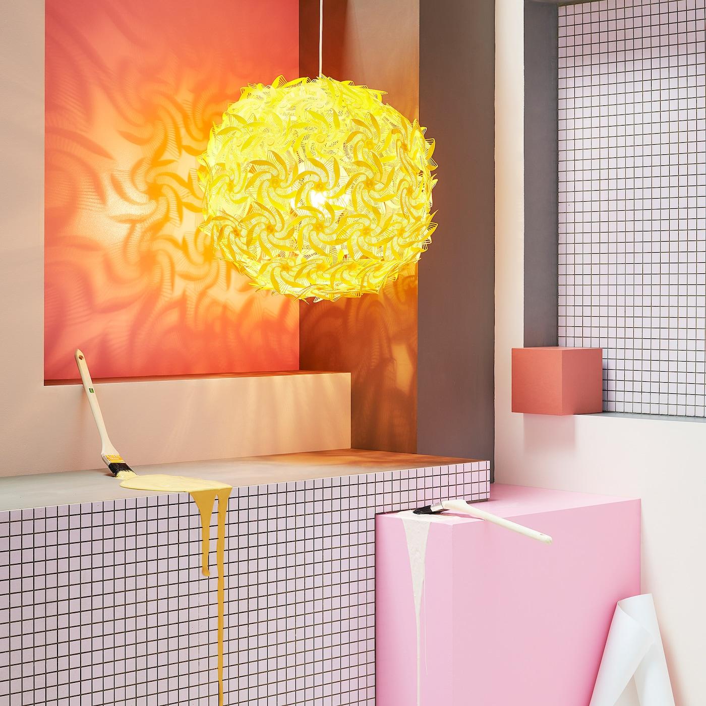 Ein Raum mit einer verspielten, gelben Hängeleuchte, karierten Wänden, Pinseln & Farbklecksen.
