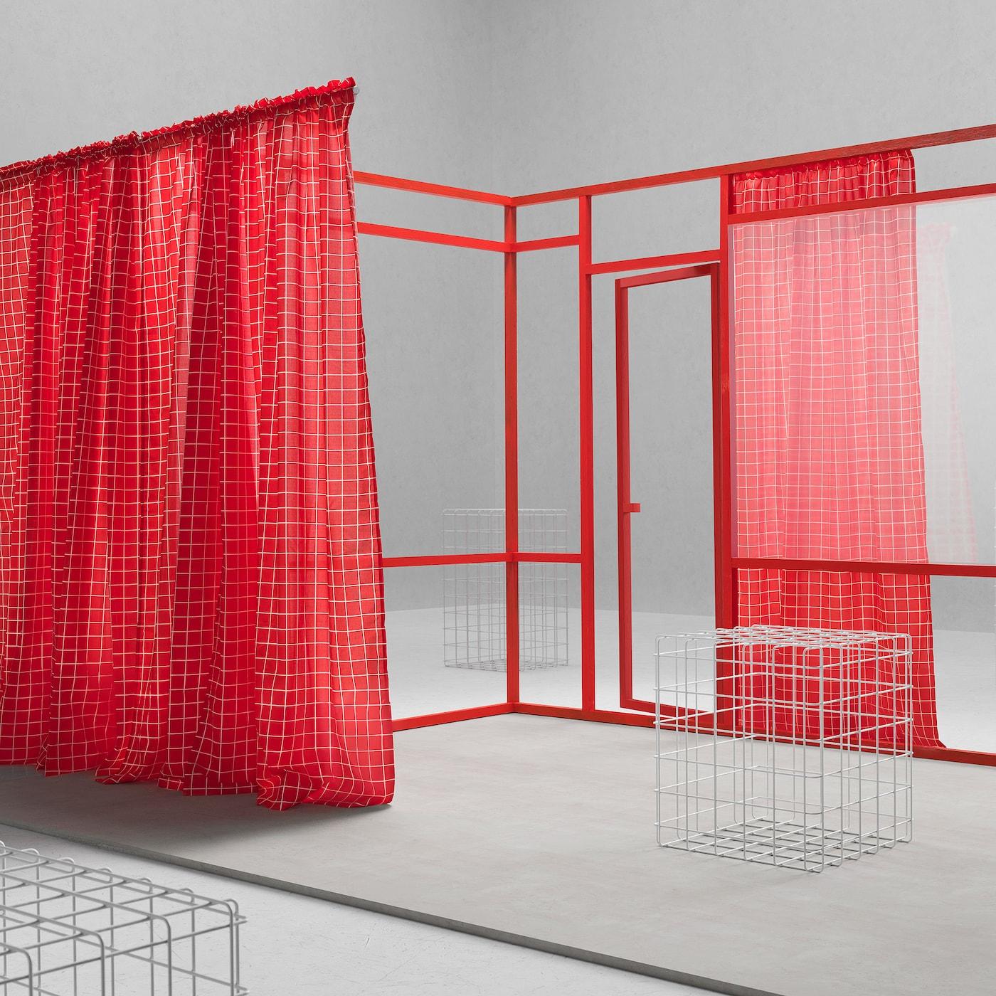 Ein Raum mit roten Vorhängen an einem roten Gestell & Würfeln aus grauem Draht.
